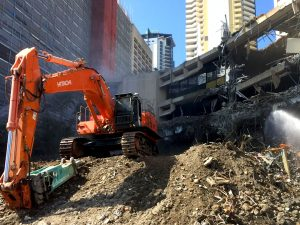 Demolition site with rock breaker and dust control